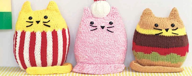 Three knitted cats lined up, the one on the left has red and white stripes, the middle one is pink and the one on the right is brown on the top and bottom with a red and darker brown section in the middle - like a burger.