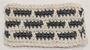 A crochet swatch that looks like brickwork, made using the mosaic crochet technique